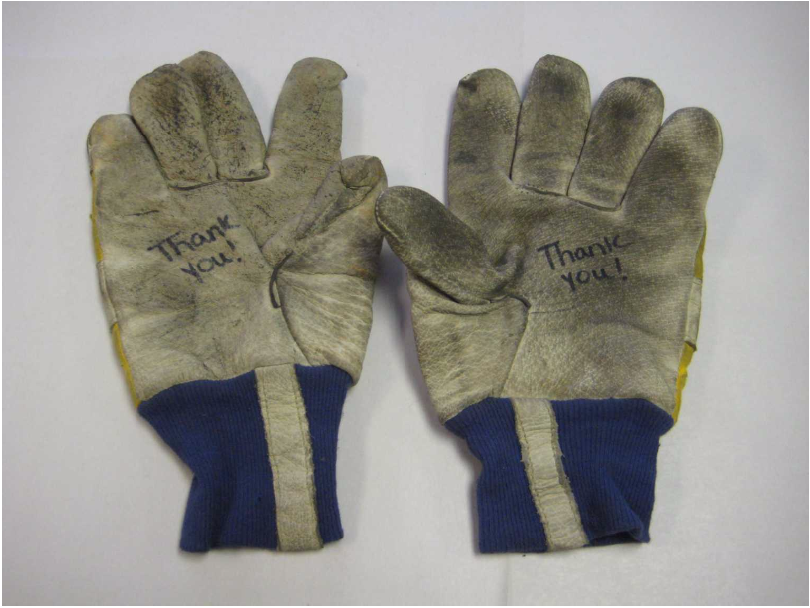 """The gloves used by Det. David Brink during the rescue and recovery operations at Ground Zero following 9/11. These gloves were donated by an unknown stranger who wrote """"Thank you!"""" on the gloves. - Photo Courtesy of 9/11 Memorial & Museum"""