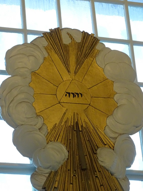 """The front of the 9/11 Church (St. Paul's Chapel) has a sculpture representing """"The Glory"""" as God's holy name in Hebrew. The light coming from the Tetragrammaton inside of clouds represents the """"Glory"""" described in Exodus 24:16-17 and Ezekiel 1:28."""