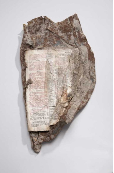 """This Bible opened to the New Testament passage containing the """"Sermon on the Mount"""" was found fused to a chunk of steel at the World Trade Center. - Photo Courtesy of 9-11 Memorial & Museum"""